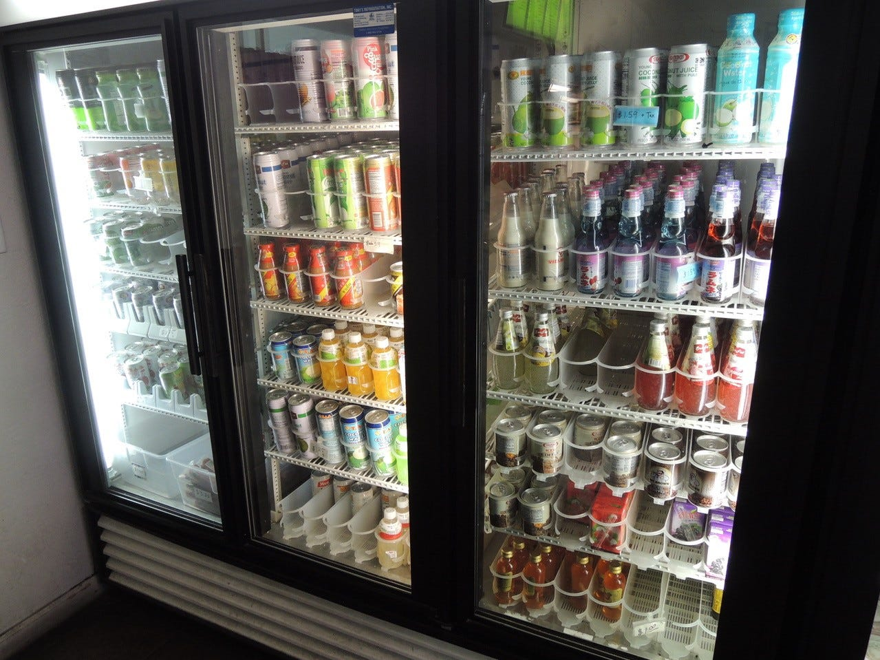 The refrigerated case offers a range of colorful and exotic beverages.