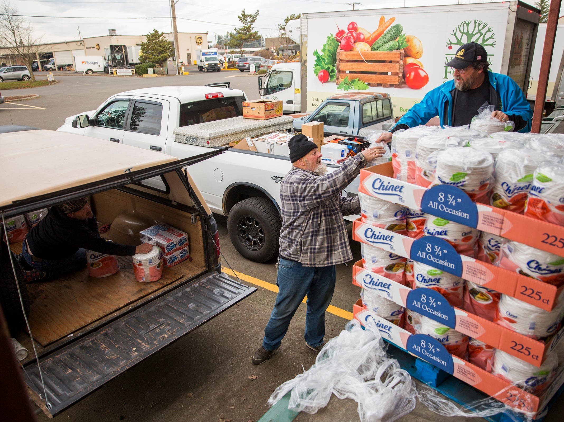 Doug Pendleton and Charlie Flynn load paper plates into a vehicle at the Marion-Polk Food Share on Friday, Dec. 7, 2018.