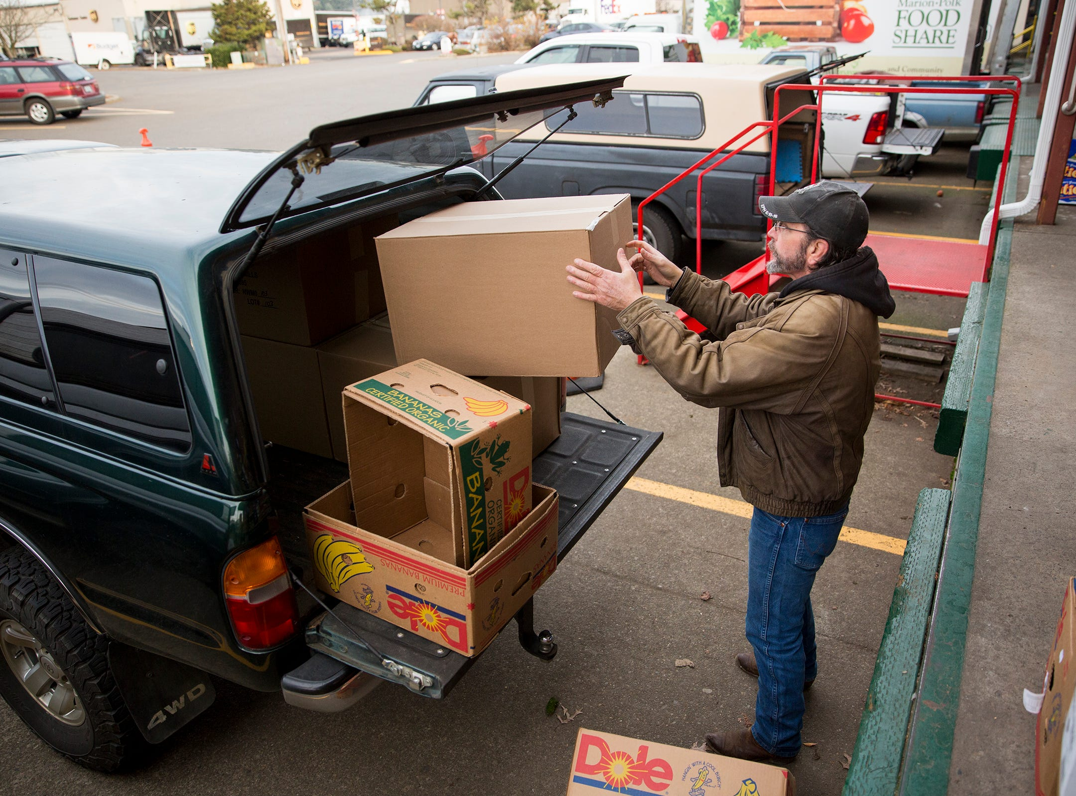 Art Scaglione loads boxes of food into his vehicle at the Marion-Polk Food Share in Salem on Friday, Dec. 7, 2018. He collects the food for homeless people living in Wallace Marine Park.
