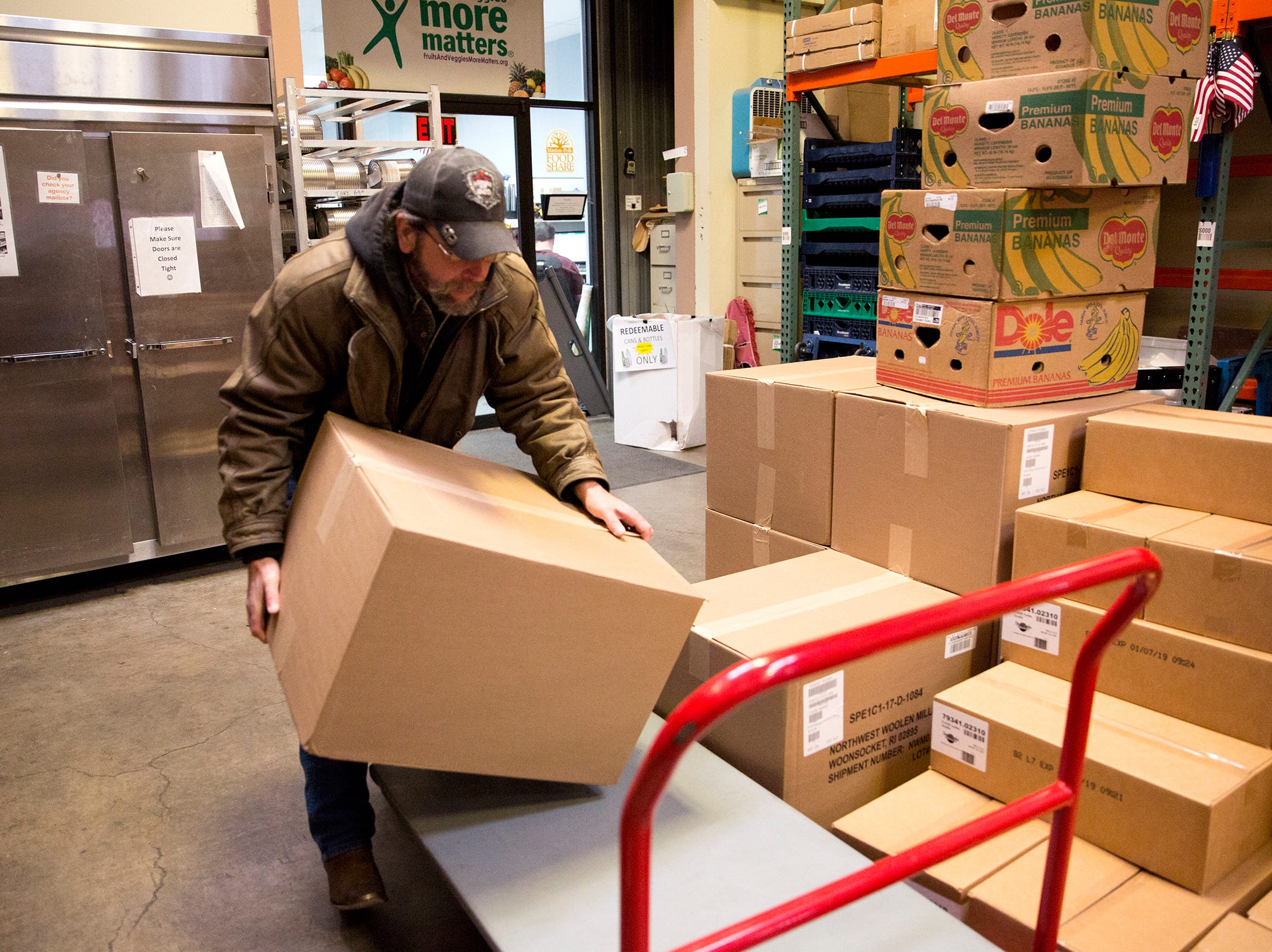 Art Scaglione loads boxes onto a crate at the Marion Polk Food Share in Salem on Friday, Dec. 7, 2018. He collects the food for homeless people living in Wallace Marine Park.