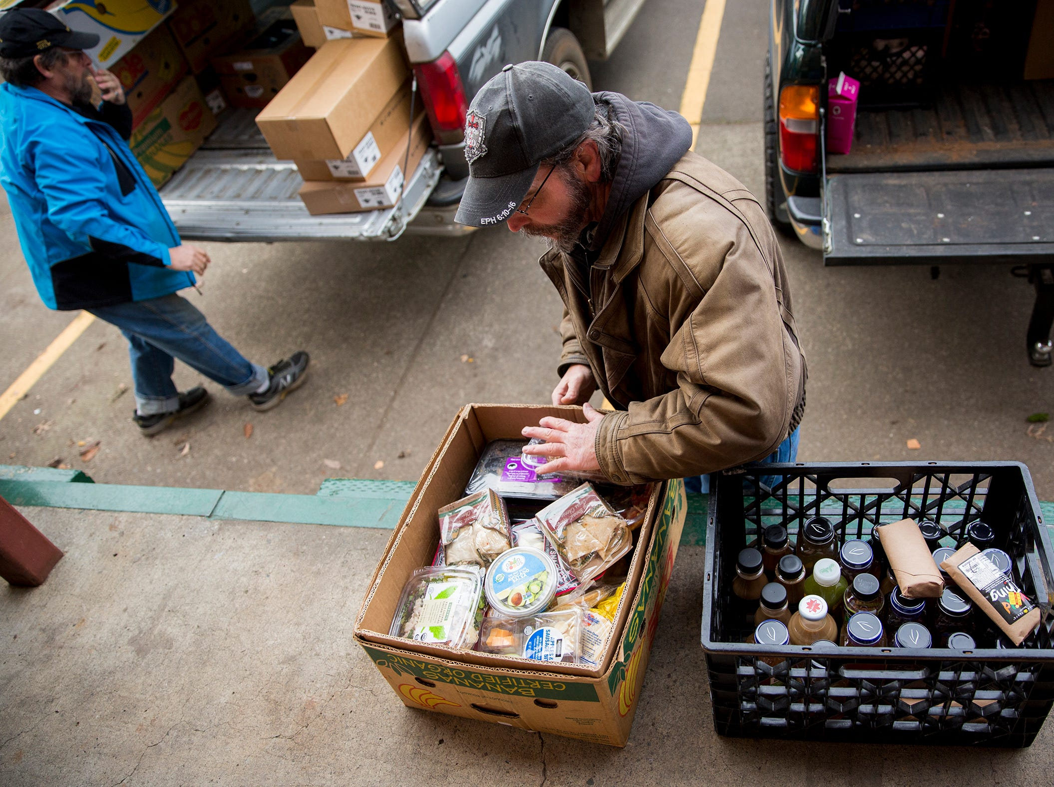 Art Scaglione sorts through food items at the Marion-Polk Food Share in Salem on Friday, Dec. 7, 2018. He collects the food for homeless people living in Wallace Marine Park.