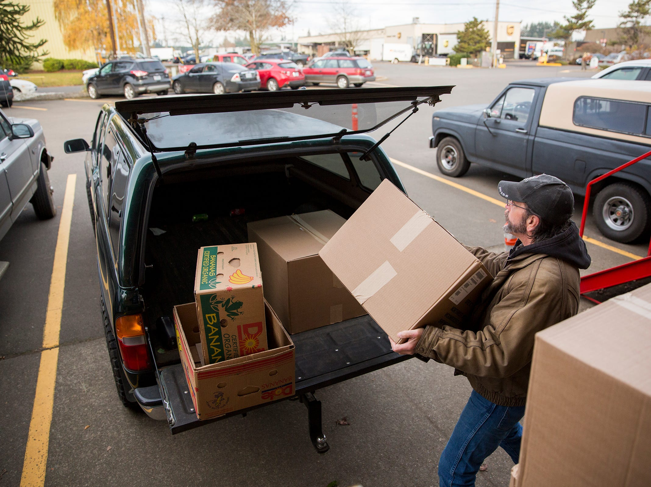 Art Scaglione loads boxes of food into his vehicle at the Marion Polk Food Share in Salem on Friday, Dec. 7, 2018. He collects the food for homeless people living in Wallace Marine Park.