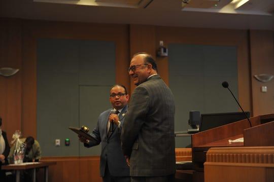 El supervisor Luis Alejo le presenta un premio al supervisor Simón Salinas durante la sesión de la junta de supervisores del martes.