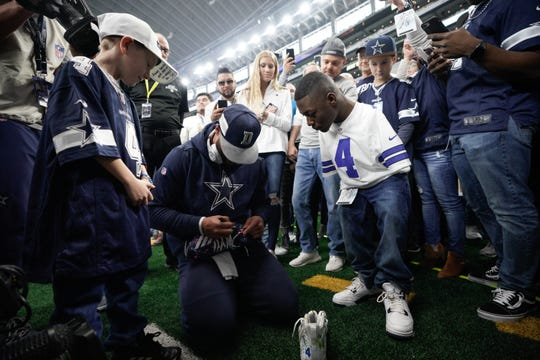 Dallas Cowboys quarterback Dak Prescott signs cleats designed by Kendrell Daniels (right) as Zane Dunn (left), from Marshall, Texas, looks on prior to Sunday's game against the Philadelphia Eagles.