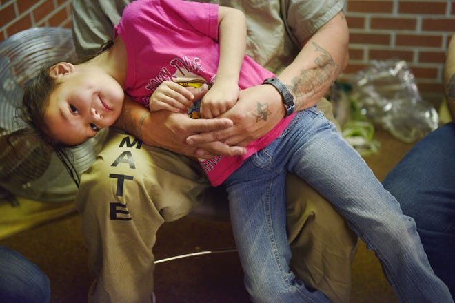 Mark Milk talks about the Family Powwows while his niece McKenna sits in his lap Saturday, Dec. 8, at the South Dakota State Penitentiary.