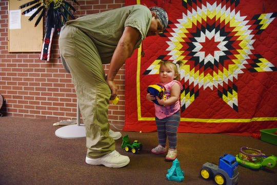 Kinsley, Mark Milk's niece, plays with Mark at the Family Powwow Saturday, Dec. 8, at the South Dakota State Penitentiary.