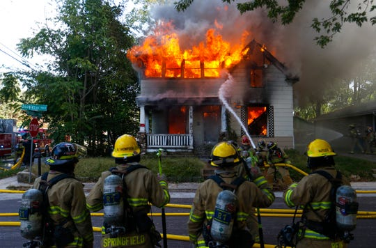 Firefighters battle a house fire at the corner of West Nichols Street and North Douglas Avenue on Wednesday, Oct. 17, 2018.