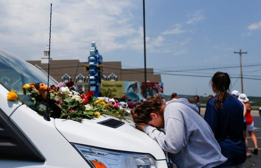 A woman prays on the hood of a van left in the parking lot of Ride the Ducks on  July 20, 2018, after a duck boat sank on Table Rock Lake, killing 17 people.