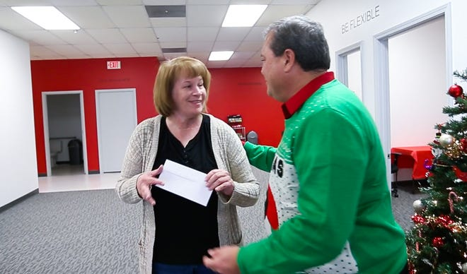 Bayada Home Health Care Division Director Aaron Anothayanontha gives a check an employee at the company office on Tuesday, Dec. 11, 2018.