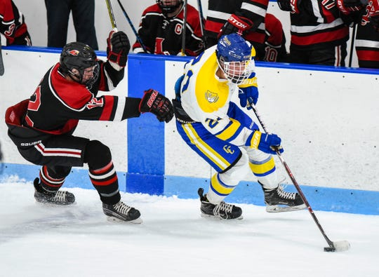St. Cloud Cathedral's Jackson Savoie takes the puck past Alexandria's Evan Lattimer during the first period Tuesday, Dec. 11, at the Municipal Athletic Complex.