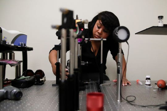 Candace Harris, a candidate for a PhD in physics from Florida A&M University, uses a nano second pulsed laser operating at 1064 nanometers to blow up a silicone sample in a lab at the Centennial Building Tuesday, Dec. 11, 2018.