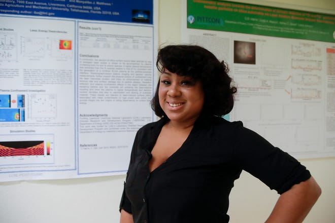 Candace Harris, a candidate for a PhD in physics from Florida A&M University, with two of her research posters, one which she presented in France and one which she presented in Chicago, at the Centennial Building Tuesday, Dec. 11, 2018.