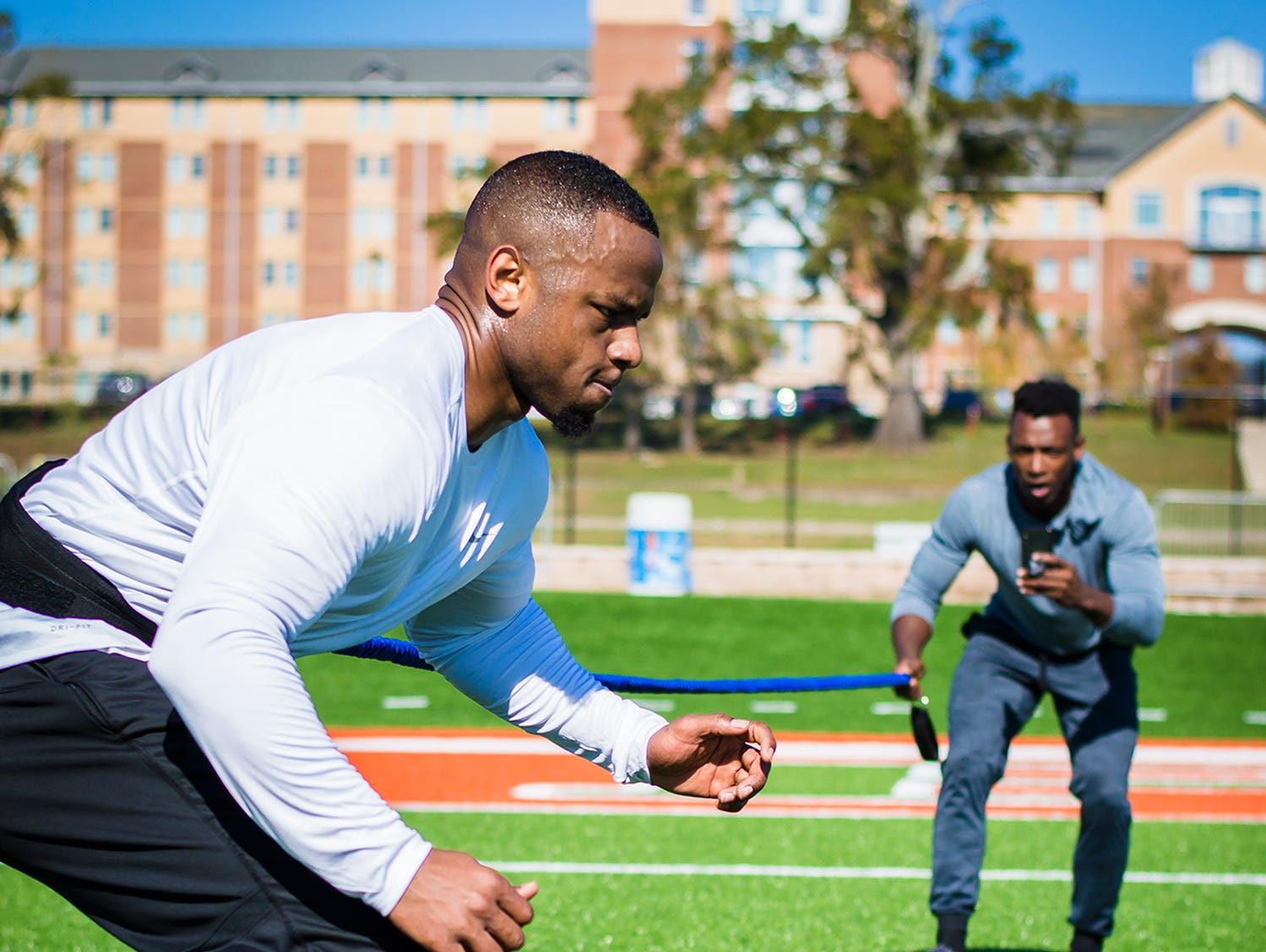 Former FAMU linebacker Akil Blount works with his former Rattlers teammate John Derae (background) on his lateral movement at Bragg Memorial Stadium.