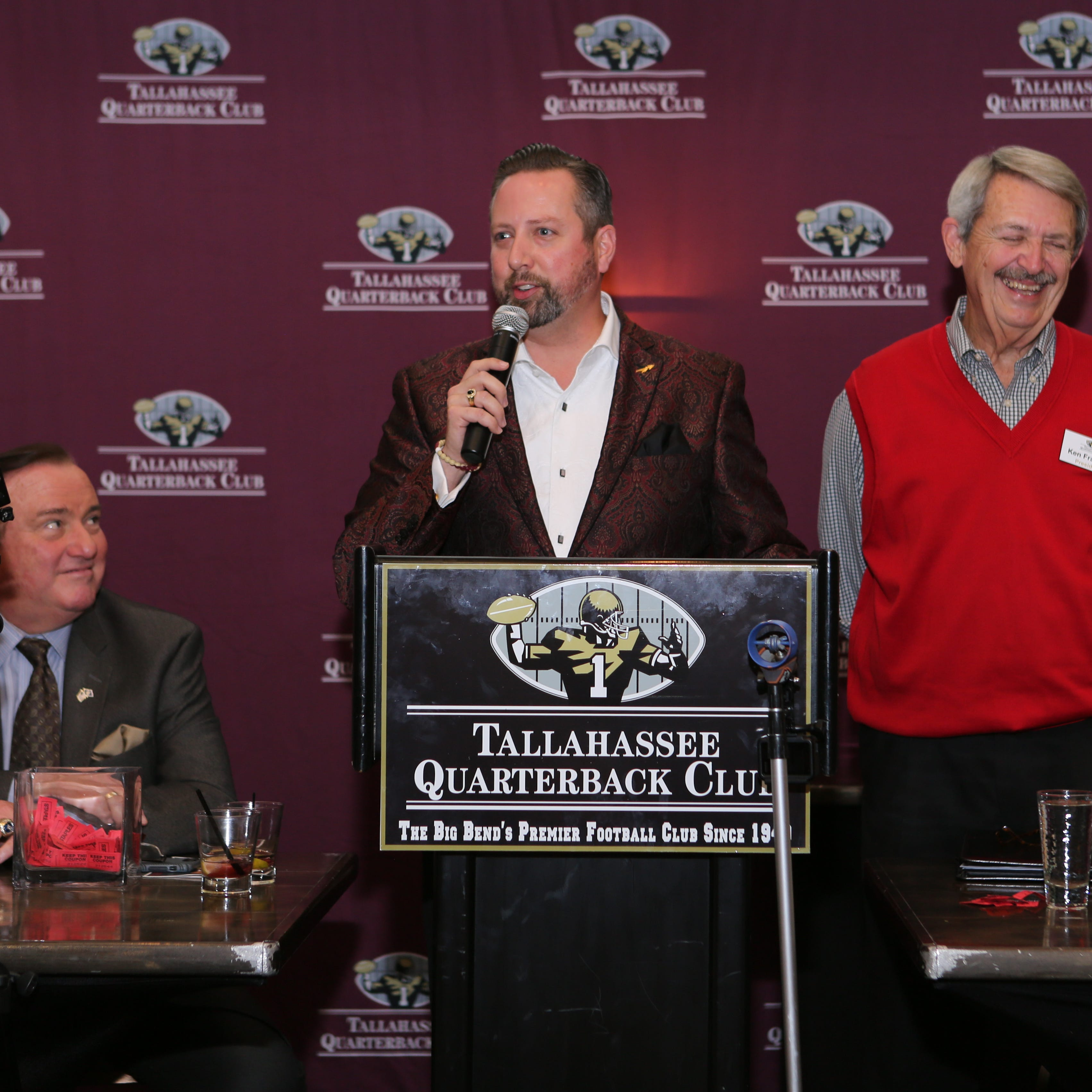 Tallahassee Quarterback Club president Hugh Tomlinson (center) addresses the crowd during the year-end jamboree with Ken Franklin (right). Tim Brando (left) was the guest speaker.
