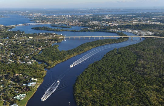 Boats cruise the South Fork of the St. Lucie River, south of the new Veterans Memorial Bridge (center) and the older Palm City Bridge.