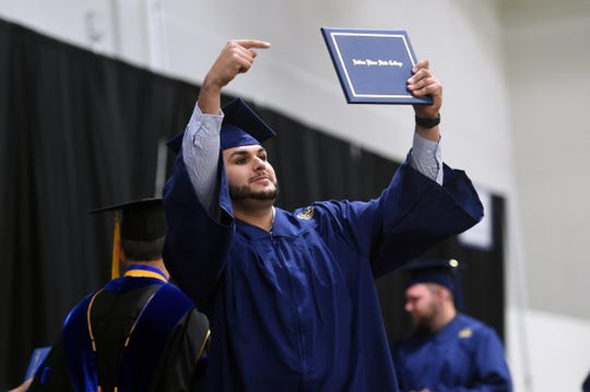 Andrew Sesta, of Stuart, points to his associate diploma on Wednesday, Dec. 12, 2018 as friends and family cheer from the audience during the fall commencement ceremony for Indian River State College in Fort Pierce.