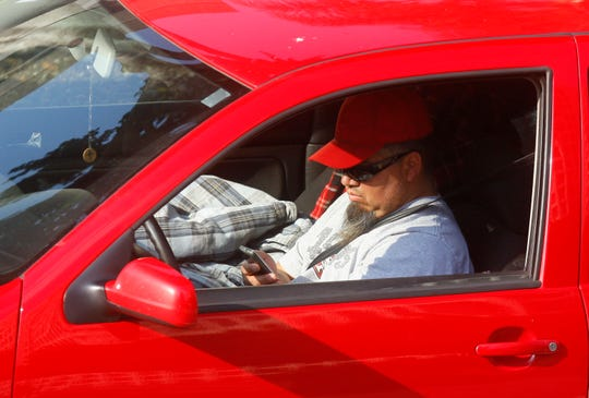 In this AP file photo, a driver uses a cellphone while driving. Virginia lawmakers voted this week to ban motorists from touching their cellphones while driving.