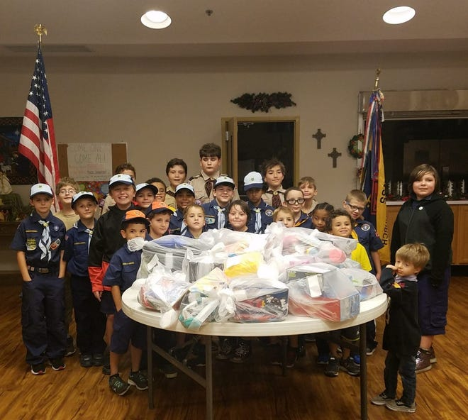 Cub Scouts of Pack 422 surround the table full of toys and clothing they shopped for, and donated to the Salvation Army.
