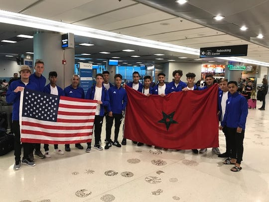 The U18 Port St. Lucie United soccer team holds both U.S. and Moroccan flags at the airport in Casablanca, Morocco.