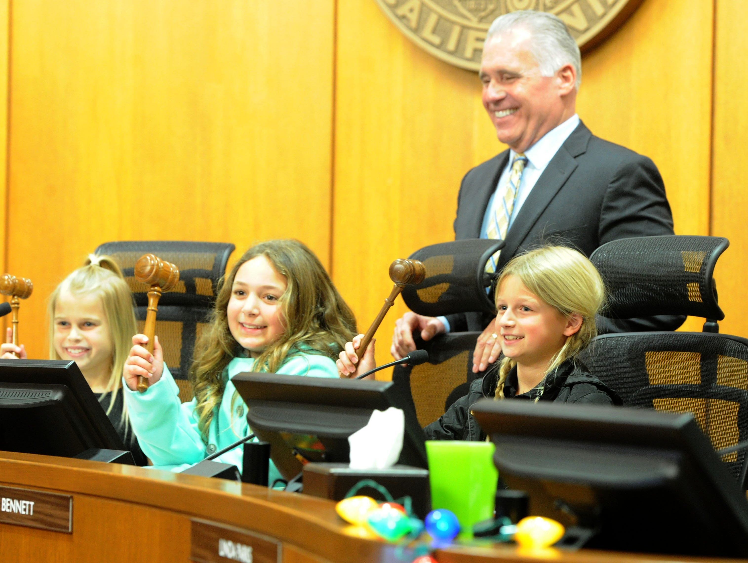 (Left to right) Brynn Baker, 7; Brielle Basson, 9; and Brooke Baker, 9, pose with their grandfather, Supervisor Peter Foy, as he is recognized Tuesday during his last meeting asa member of the Board of Supervisors.