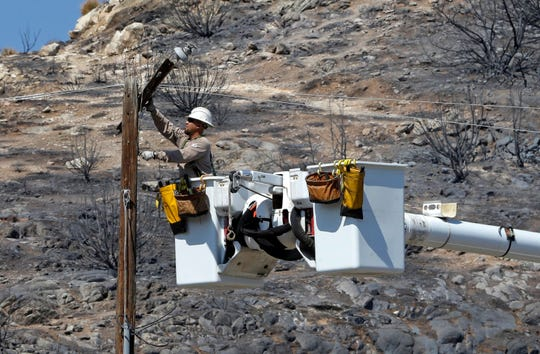 In this June 27, 2016, file photo, Robert Delgado, a lineman for Southern California Edison, works on a power line at fire ravaged South Lake.
