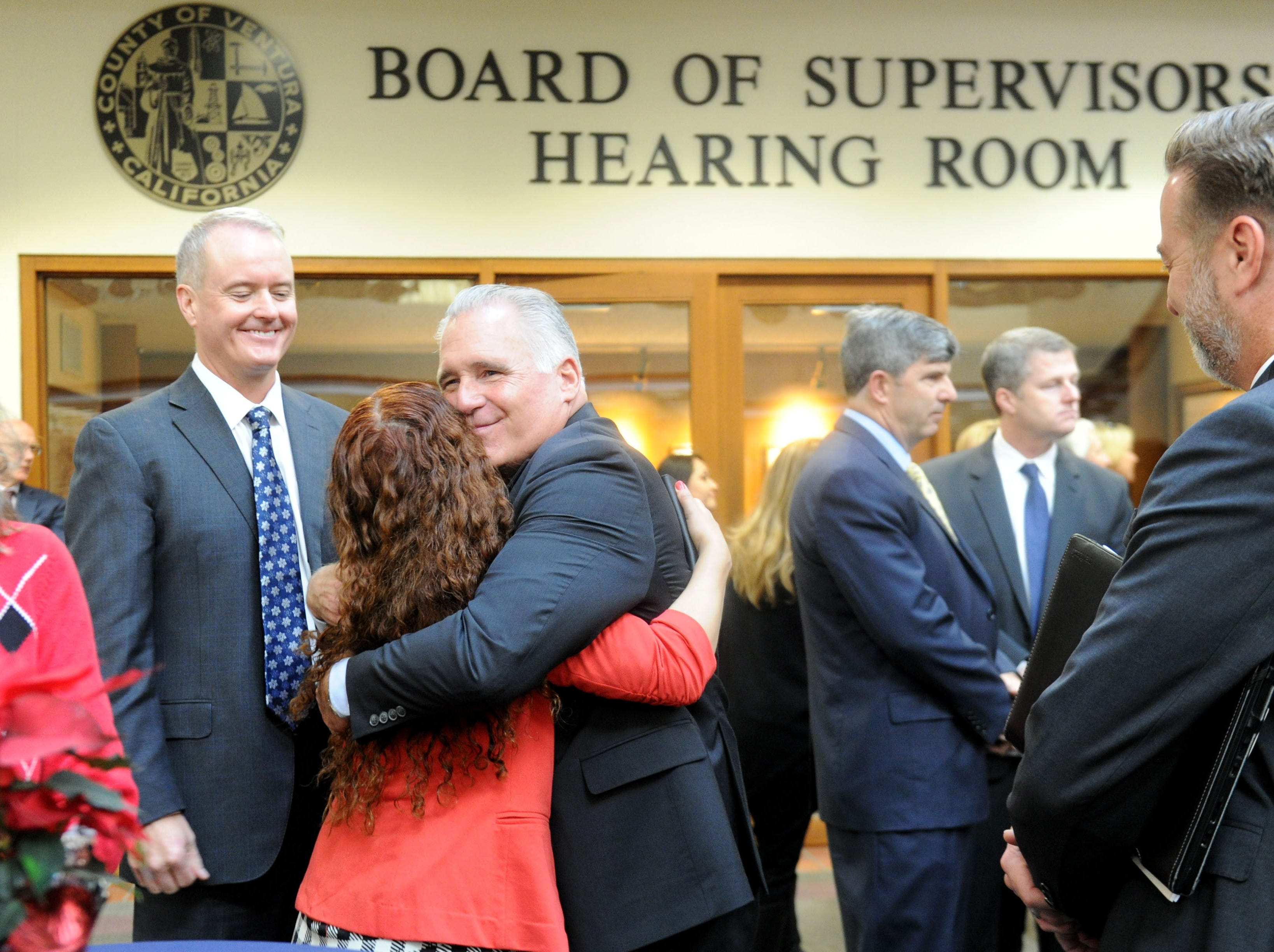 County Executive Officer Mike Powers watches as his executive assistant, Veronica Gonzalez, hugs Supervisor Peter Foy at his going-away reception outside the Board of Supervisors hearing room.