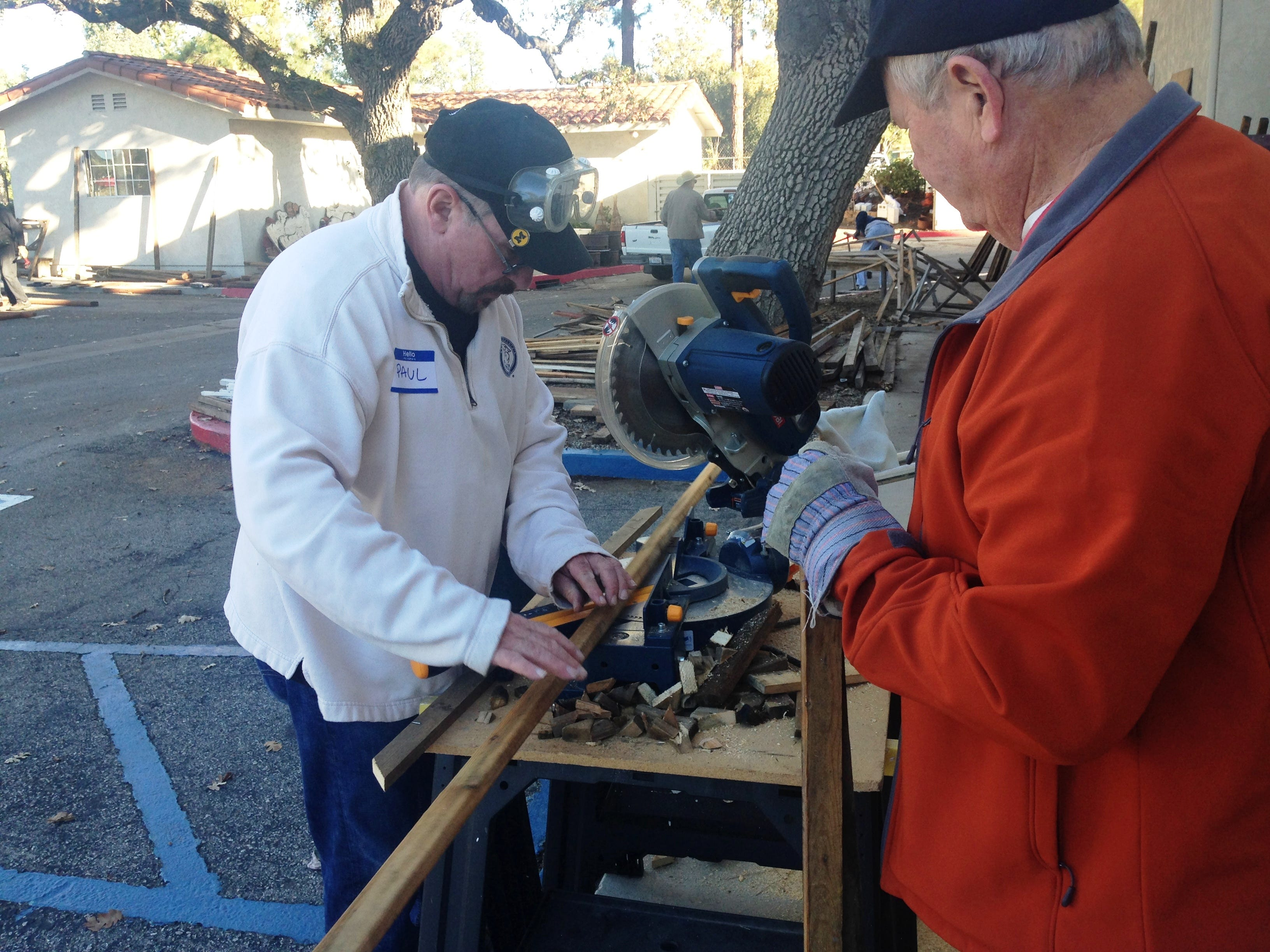 Volunteer Paul Diggs uses a saw to build the sets for the Bethlehem Experience as volunteer Ed Wohlenberg looks on.