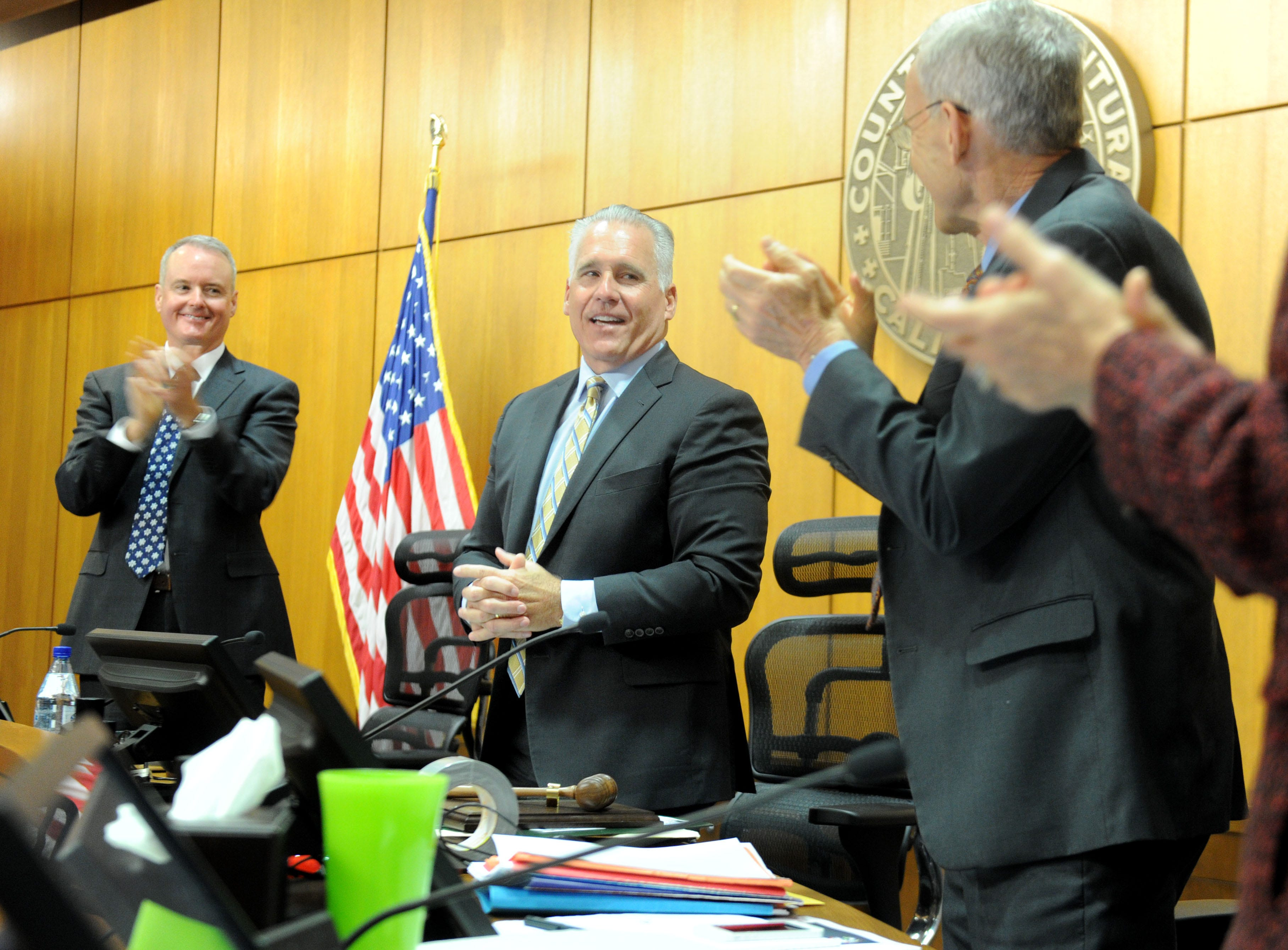 County Executive Officer Mike Powers and Supervisor Steve Bennett congratulate Supervisor Peter Foy (center) as he receives a standing ovation during a recognition ceremony Tuesday in Ventura. The occasion marked Foy's last meeting as a member of the Ventura County Board of Supervisors.