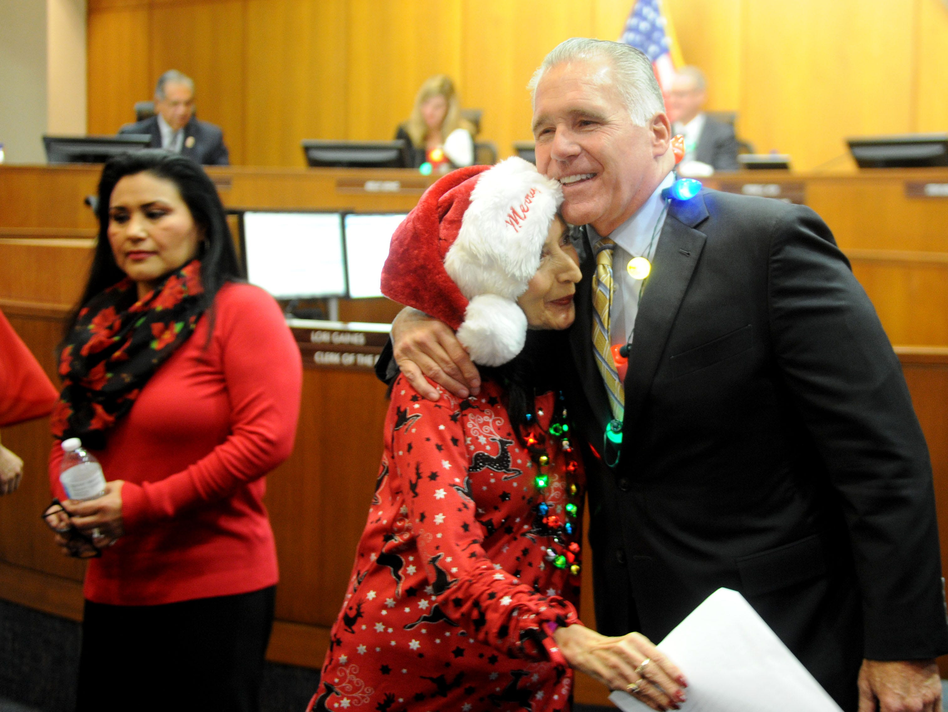 Retiree Olivia Lopez, a member of the County Christmas Carolers, hugs Supervisor Peter Foy after the group sings to him. The occasion marked Foy's last board meeting as a county supervisor. His term ends Jan. 7.