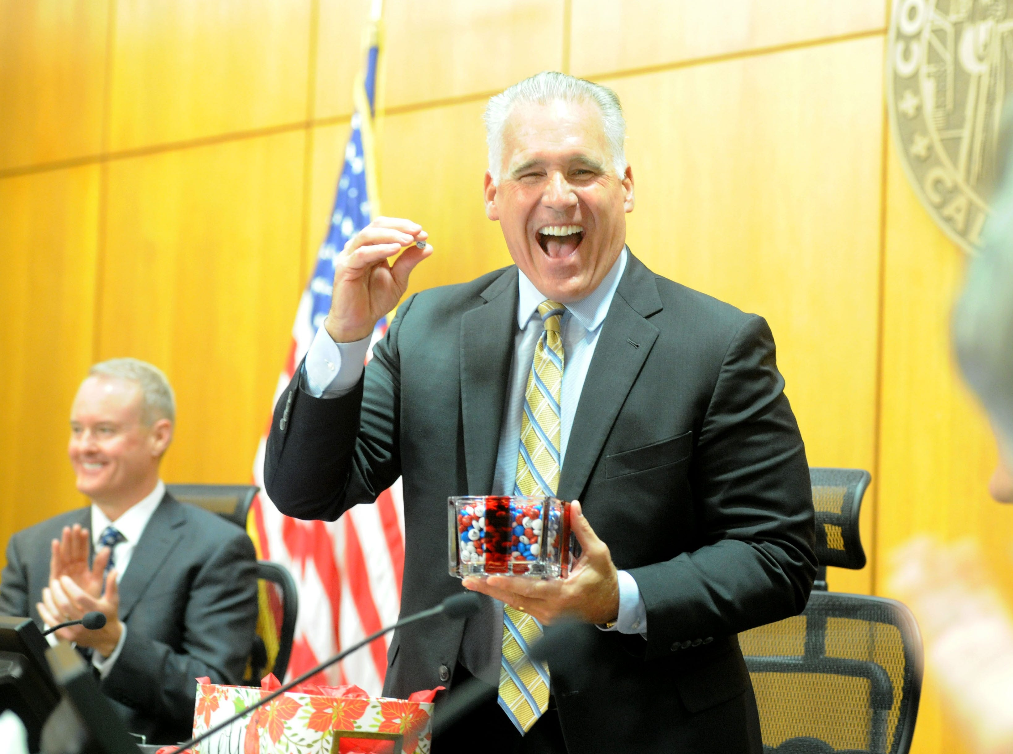 Supervisor Peter Foy looks at Supervisor Linda Parks after she gives him a package of M&M's with his face on them at Foy's last meeting Tuesday as a member of the Board of Supervisors.
