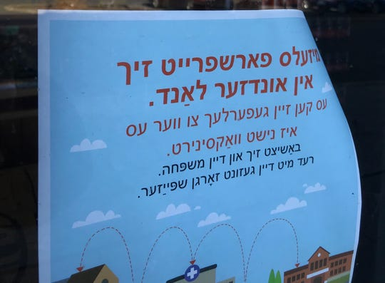 A sign in Yiddish outside Compare Supermarket in Spring Valley, where a person with measles visited in November. Signs in English, Spanish, French Creole and Yiddish explained the possible exposure to the virus.