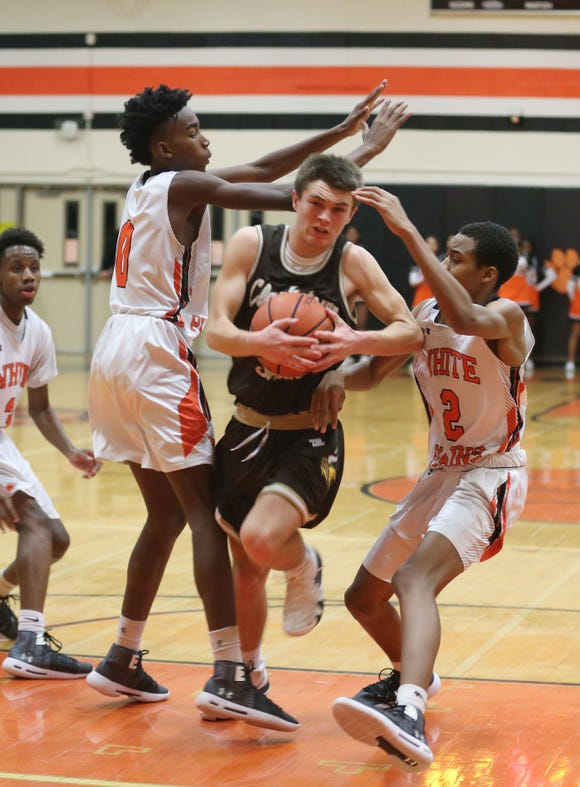 Clarkstown South's Jack Tucek (00) tries to muscle his way through White Plains' Quion Burns (0) and Eisaiah Murphy (2) during boys basketball action at White Plains High School Dec. 11, 2018. White Plains won the game 64-56.