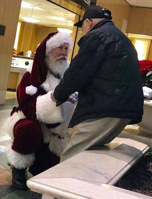 Santa kneels down to thank World War II veteran Bob Smiley for his service.