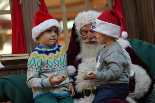 John Hughes, 5, and his brother Aaron, 3, sit on the lap of Concord Mall's Santa Claus as they tell him their Christmas wishes.