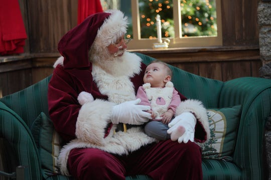 The Concord Mall Santa holds 5 month-old Mable Costill during a visit to the mall with her mother Mattie.
