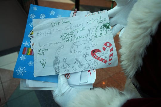 The Concord Mall Santa Claus holds some of his favorite letters to him with Christmas messages from young children.