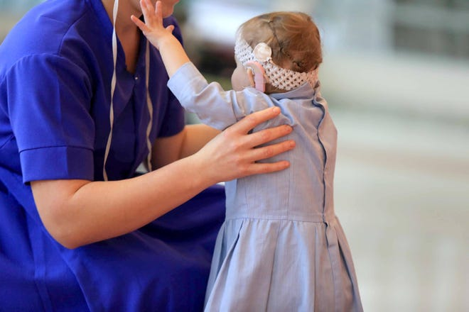 2 year-old Grace reaches for her mother Thelma while taking a walk after an occupational therapy session at Nemour/A.I. duPont Hospital for Children.