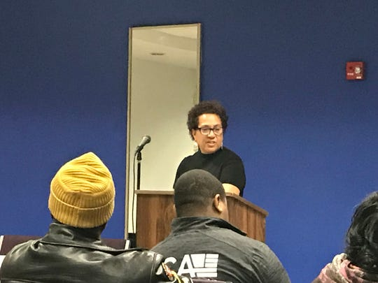 Subira Ibrahim, who applied for the 1st District council seat, speaks to residents at a meeting Tuesday night at the Police Athletic League center.