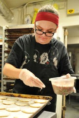 Margie's Sweet Shop, decorator, Madi Cantrell prepares sugar cookies to be sprinkled Tuesday afternoon in their bakery located on Call Field Rd.