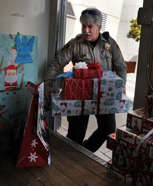 Wichita County Deputy Scott Chapel loads Angel Tree gifts for local children in need Wednesday afternoon.