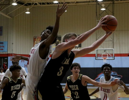 Rider's Ben Moffat grabs the rebound Hirschi's Gabe Colbert Tuesday, Dec. 11, 2018, at Hirschi. The Raiders defeated the Huskies 55-37.