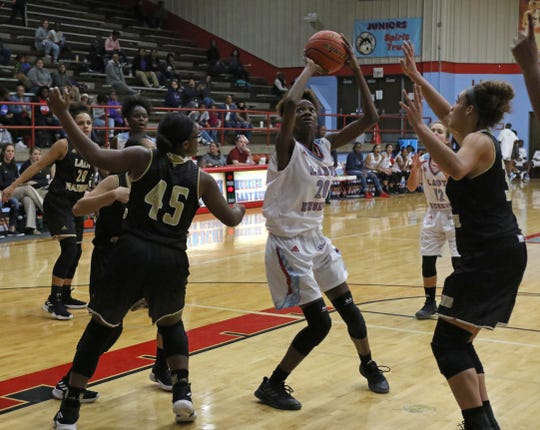 Hirschi's Niara Hightower looks to the basket surrounded by Rider defenders Tuesday, Dec. 11, 2018, at Hirschi. The Lady Huskies defeated the Lady Raiders 51-35.