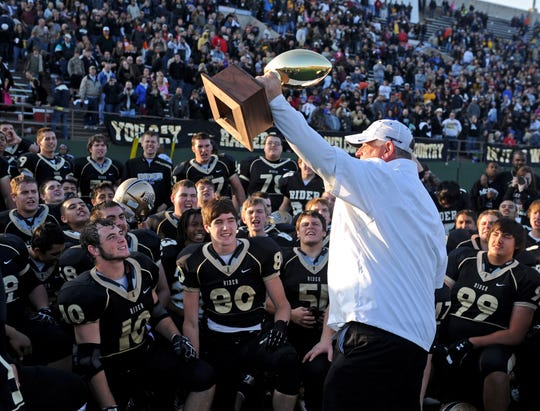 Former Rider head football coach Jim Garfield hoists the Region I-4A championship trophy in front of his players and the Raider fans at Memorial Stadium after the program won its first trip to the state semifinals in 2012, beating Frenship 33-7.