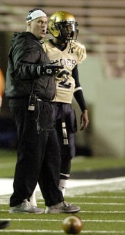 Rider head coach Scott Ponder talks with quarterback Shavodrick Beaver before an offensive series during the 2006 Region I-4A final against Frenship at Jones Stadium in Lubbock.