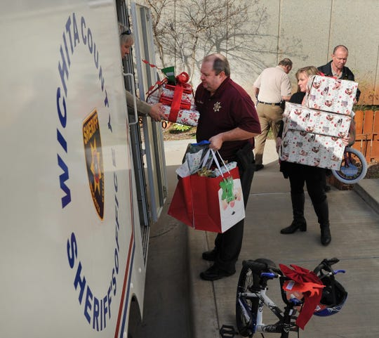 Wichita County courthouse employees and county deputies work to load-up donated Angel Tree toys to be delivered to underprivileged children for Christmas.