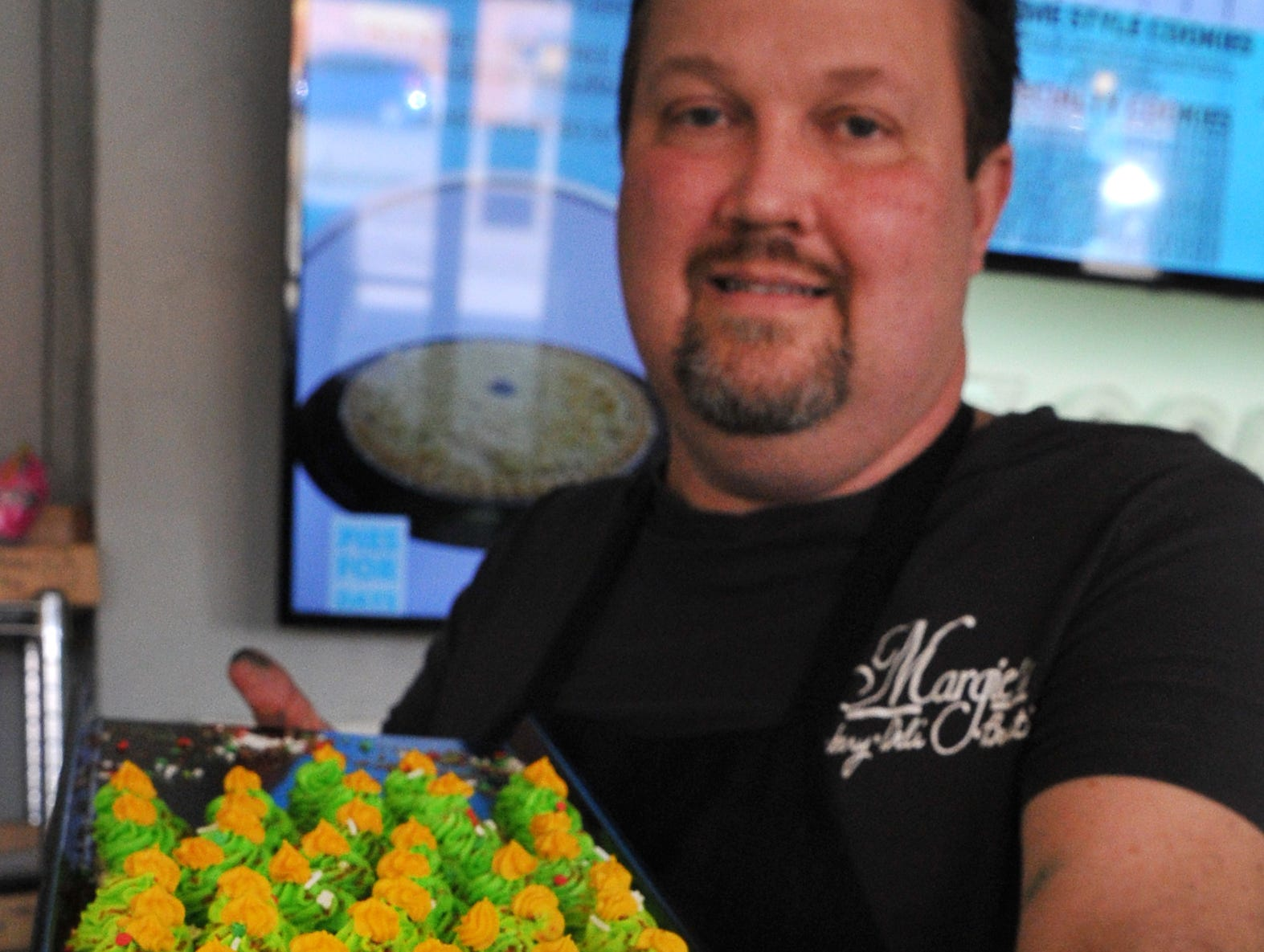 Margie's Sweet Shop, Owner, Michael Gerstner displays one of his bakery's most favored treat, Icing Thumb Prints.