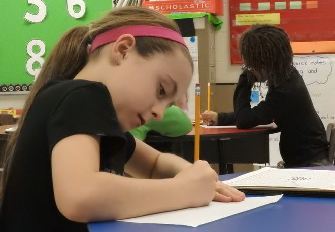 Taylor Wyatt, a third grade student at National Road Elementary School, practices her persuasive writing on Dec. 12, 2018.