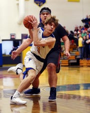 Kalob McElhaney, of Philo, tries to drive by Morgan's Chance Myers during the second quarter of the Electrics' 56-55 loss on Tuesday at the Power Plant.