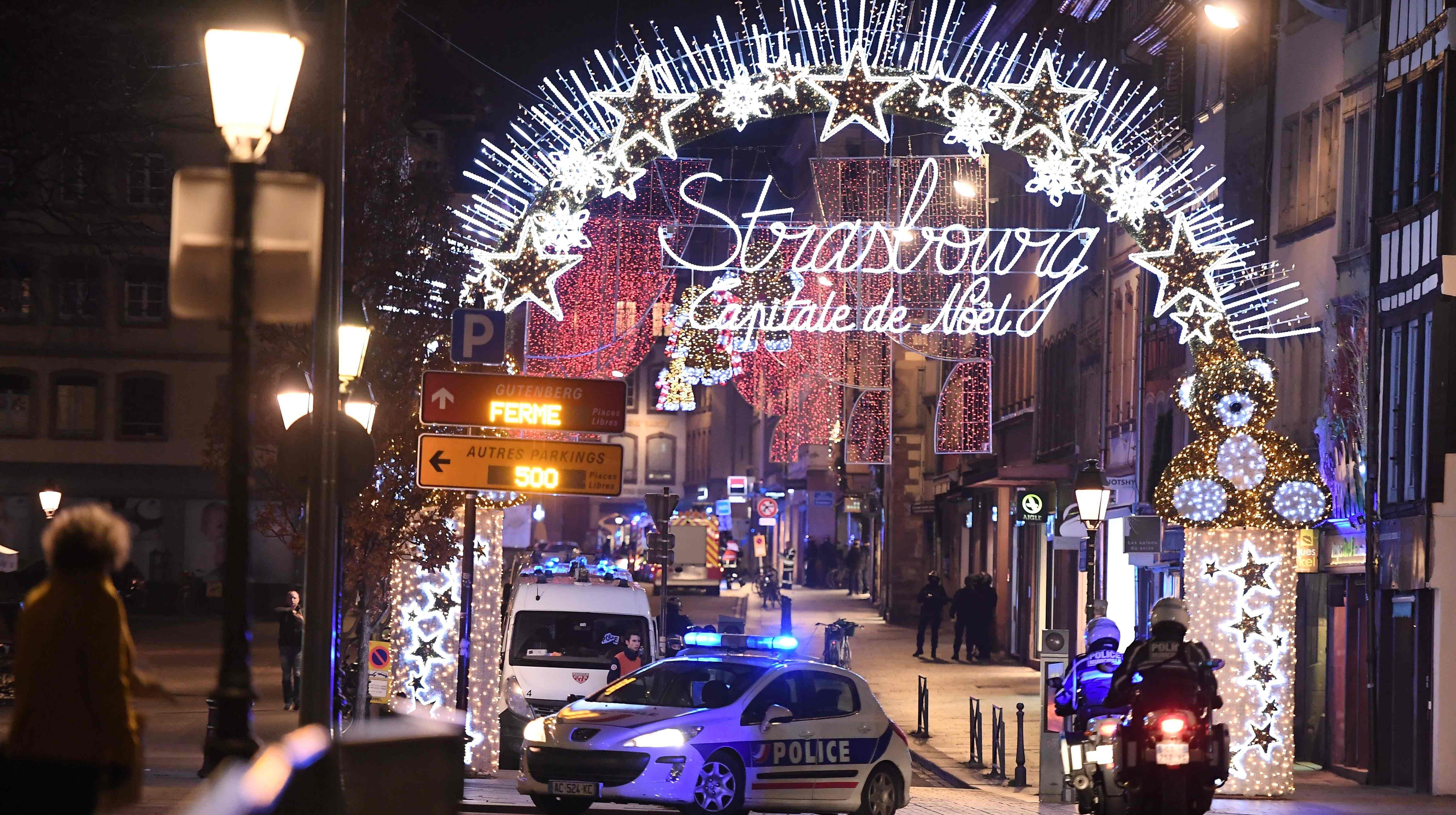A police car is parked blocking traffic in the French city of Strasbourg after a gunman killed at least four people and wounded 11 others in a suspected terrorist attack, according to police union officials.