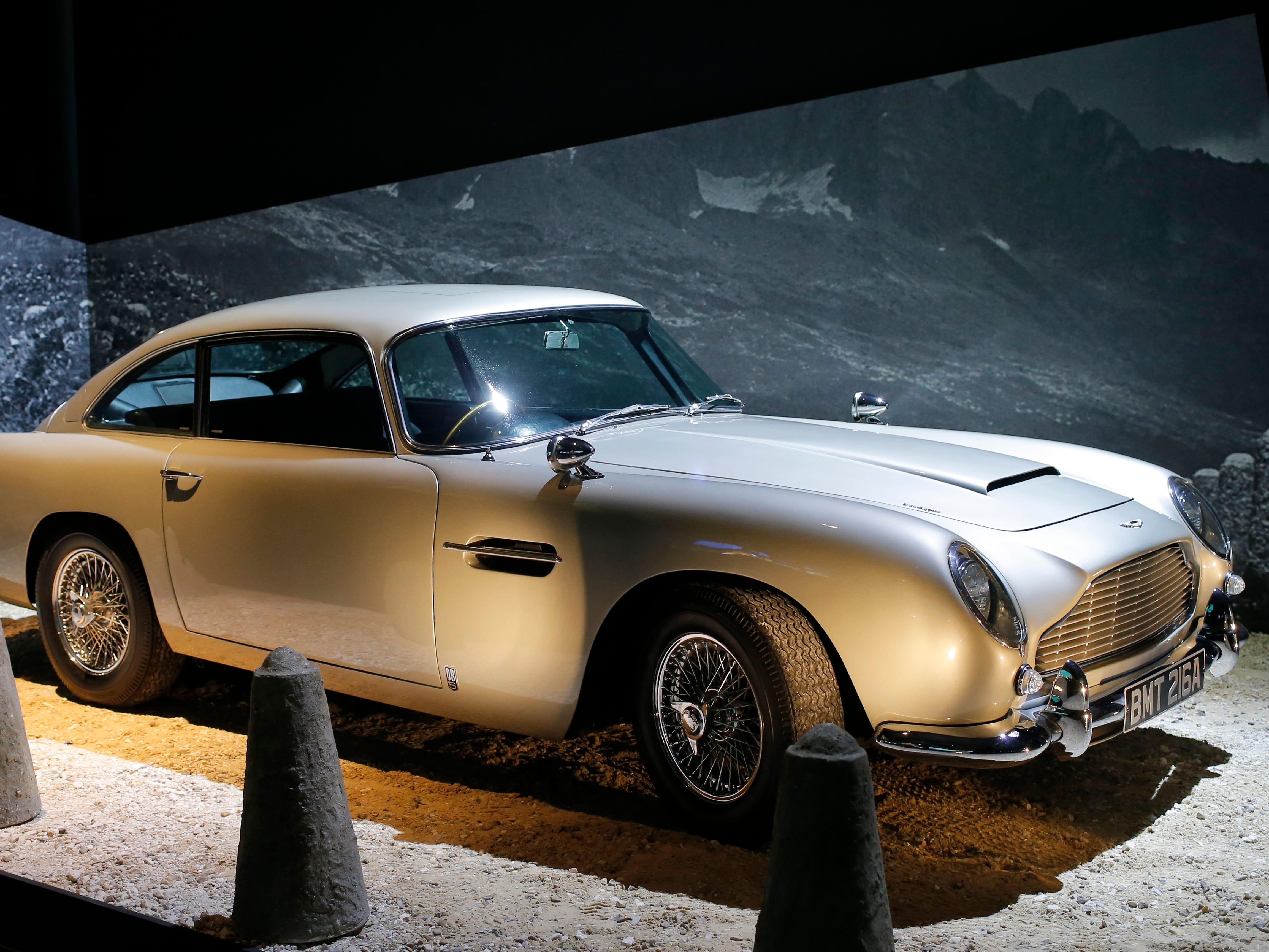 """An Aston Martin DB5 from the James Bond film """"Goldfinger"""" is displayed during a press presentation of the exhibition """"The Designing 007: Fifty Years of Bond Style"""" at the Grande Halle de la Villette in Paris, France, Wednesday April 13, 2016. (AP Photo/Francois Mori)"""